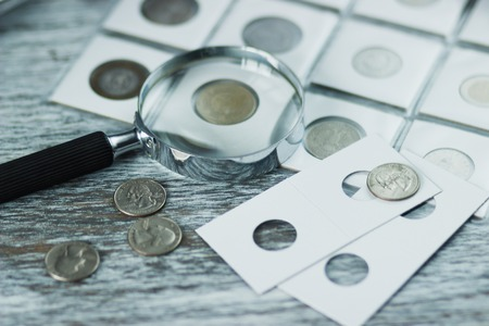 Different sizes coins in the pocket page and magnifying glass on the wooden table, Soft focus background