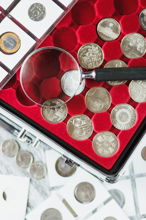Different sizes coins in the pocket page, box and magnifying glass on the wooden table, Soft focus background