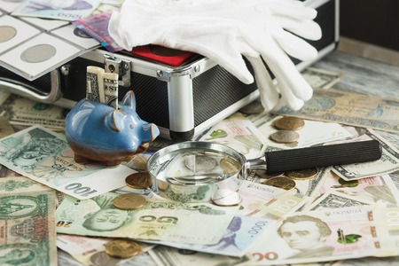 Different collectors coins and banknotes with a magnifying glass and piggy bank, wooden background