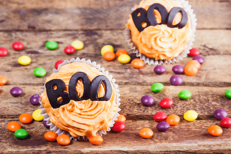 Halloween cupcakes with decorations: word boo made from confectionery mastic, soft focus background