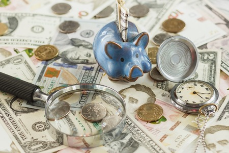 Different collectors coins and banknotes with a piggy bank, clock and magnifying glass, soft focus background Stock Photo