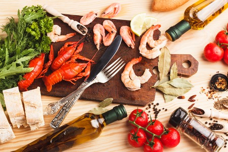 Set from silverware on the board, different spices, boiled cancers, cherry tomatoes and olive oil bottles on the wooden background Stock Photo