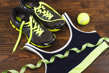 Sports items: sneakers, ball and tape measuring on the wooden background