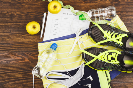 Sports items: sneakers, clothing, bottle of water and headphones on the wooden background