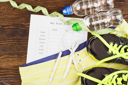 Sports items: sneakers, clothing, bottle of water and tape measuring on the wooden background Stock Photo