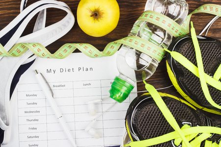 Sports items: sneakers, sport bra, bottle of water and diet plan on the wooden background Stock Photo