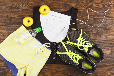 Sports items: sneakers, t-shirt, bottle of water and diet plan on the wooden background Stock Photo - 72658779