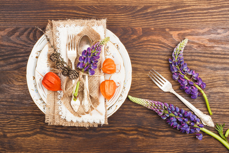 Tableware with Physalis, Lupines and silverware on the wooden background