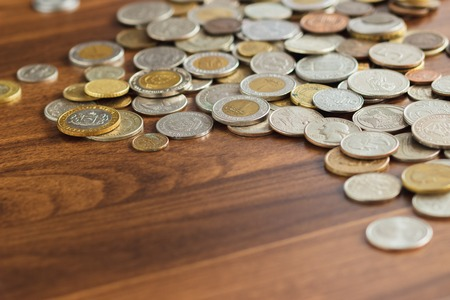 Different gold nad silver collectors coins on the wooden table, soft focus background