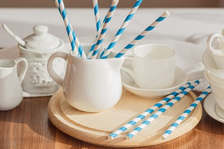 Set of white empty tableware with striped tubules, wooden background Stock Photo