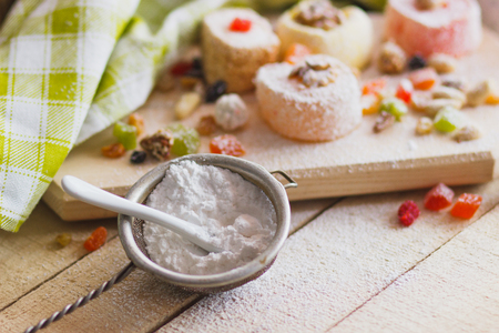 Set of rahat lokum with candied peels, nuts and sugar powder, soft focus background Stock Photo