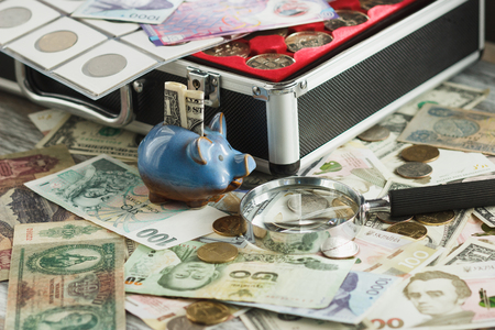 Different collectors coins and banknotes in the box, with a magnifying glass and piggy bank, soft focus background Stock Photo