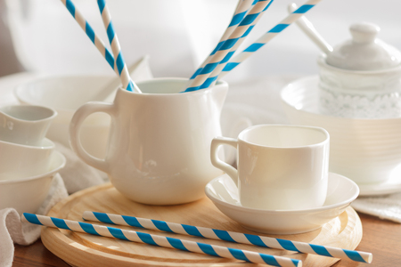secular: Set of white empty tableware with striped tubules, soft focus background Stock Photo
