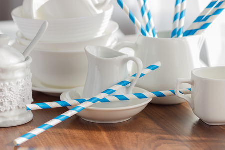 Set of white empty tableware with striped tubules, soft focus background Фото со стока