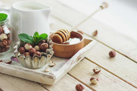 Honey in the wooden bowl, mint leaves, hazelnuts and jar with milk on the wooden tray, soft focus background Stock Photo