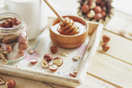 Honey in the wooden bowl, hazelnuts and jar with milk on the wooden tray, soft focus background