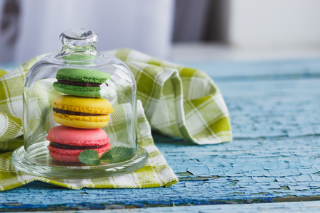 Green, pink and yellow french macarons under the glass on the wooden boards, soft focus background Stock Photo