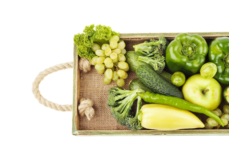 ration: Set of different green fresh raw vegetables and fruits in the wooden tray, isolated on white