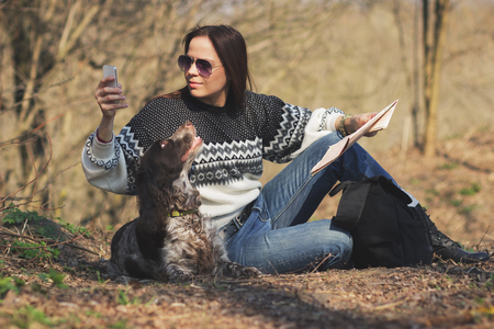 Beautiful woman brunette and brown cocker spaniel in the forest, soft focus background Stock Photo