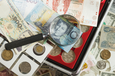 Different collectors coins and banknotes with a magnifying glass, soft focus background