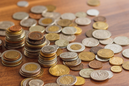 Different gold and silver collectors coins on the wooden table, soft focus background