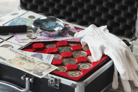 Different collectors coins in the box with a magnifying glass and white gloves, soft focus background Stock Photo