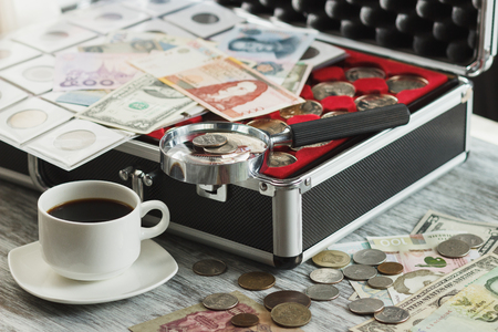 Different collectors coins and banknotes with a magnifying glass, box for coins and cup of coffee, soft focus background Stock Photo