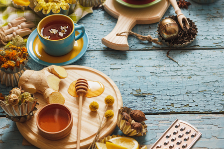 Cups with herbal tea and pieces of lemon, dried herbs and different decorations, on the wooden background Reklamní fotografie