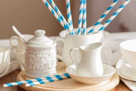 Set of white empty tableware with striped tubules, soft focus background Stock Photo