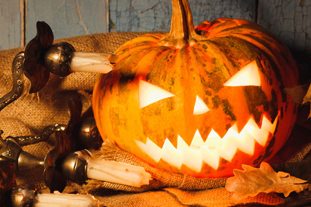 Halloween pumpkin with light from inside. Candle holder with candles and dry leaves on the wooden background