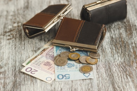 Polish zloty with little wallets on the old wooden background, soft focus background Zdjęcie Seryjne