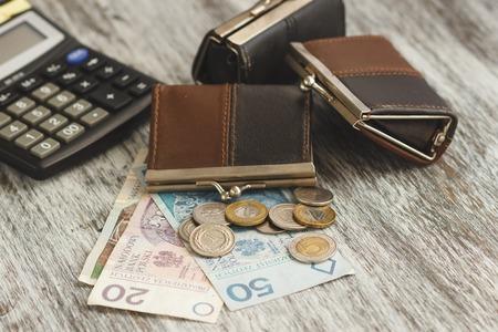 약간의 지갑과 목조 배경, 소프트 포커스 배경에 계산기와 폴란드 즐 로티
