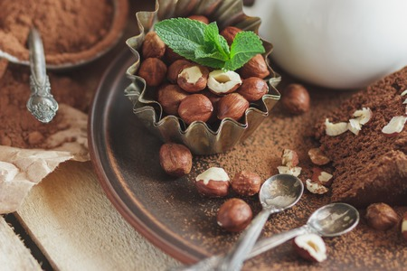 Piece of chocolate cake, mint leaves, hazelnuts and jar with milk, soft focus background