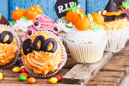 Halloween cupcakes with colored decorations: tombstone, witch hat and pumpkins made from confectionery mastic, soft focus background