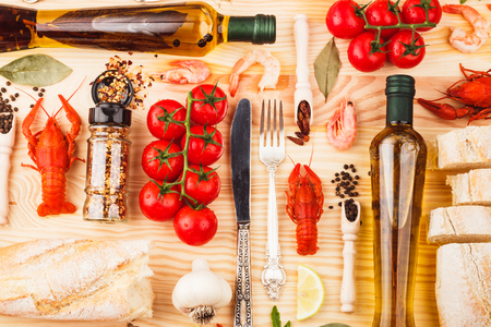 Big set from silverware, different spices, boiled cancers, cherry tomatoes, greenery and olive oil bottles on the wooden background