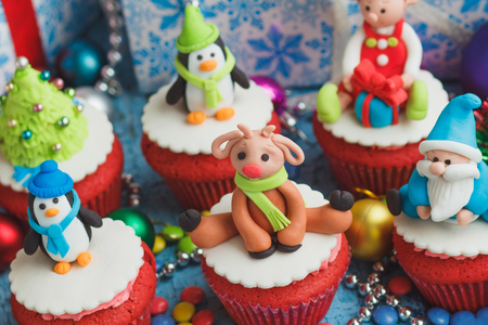 Christmas cupcakes with colored decorations made from confectionery mastic, soft focus background