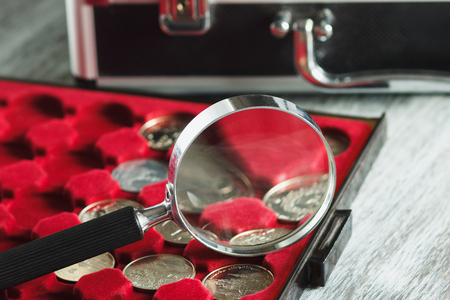 Different collector's coins in the box for coins and a magnifying glass, soft focus background 스톡 콘텐츠