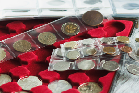 Different collectors coins in the box for coins and page with pockets, soft focus background Stock Photo