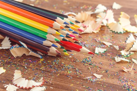 Set of colored pencils with shavings on the wooden background Stock Photo