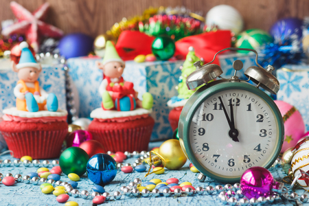 Green alarm clock and Christmas cupcakes with decorations made from confectionery mastic, soft focus background