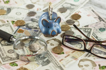 Different coins and banknotes with a magnifying glass, glasses and piggy bank, wooden background