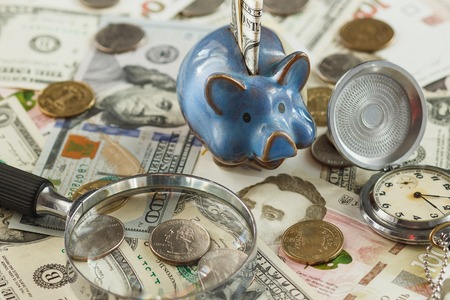 Different collectors coins and banknotes with a piggy bank and magnifying glass, soft focus background