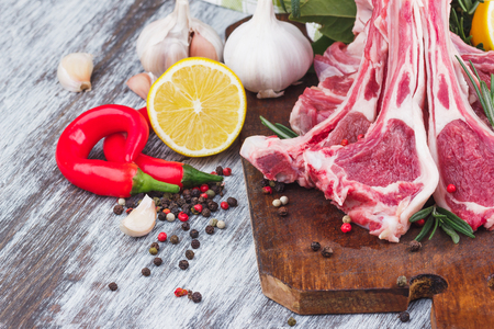 Raw lamb chop on the wooden board, soft focus background Stock Photo