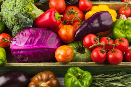 Set of different fresh raw colored vegetables and fruits in the wooden tray, light background 写真素材