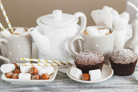 Cups with cacao and marshmallow, cupcakes and different decorations, soft focus background Stock Photo