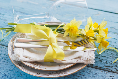 Set of tableware and a bouquet of yellow narcissus, soft focus background Stock Photo
