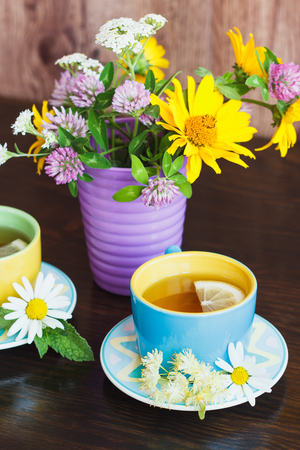 Cups of herbal tea with camomile, lemon and mint leaves on the wooden background