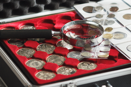 Different collectors coins in the box with a magnifying glass, soft focus background