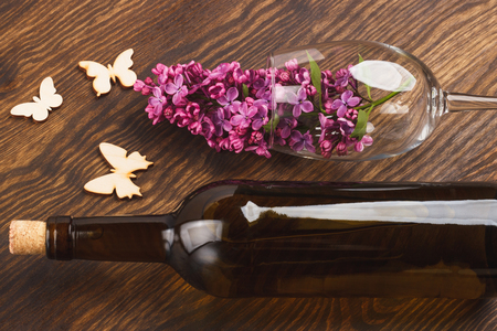 Wineglass with lilacs and butterflies decorations on the wooden background Archivio Fotografico - 119808399