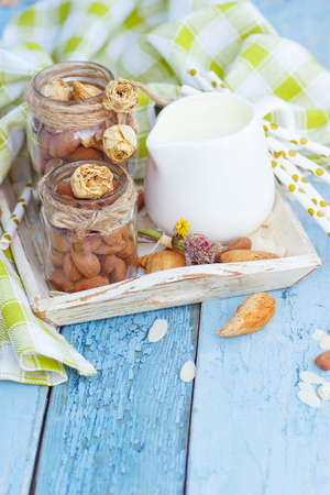 Almonds and jar with milk on the wooden tray, blue wooden background Stok Fotoğraf